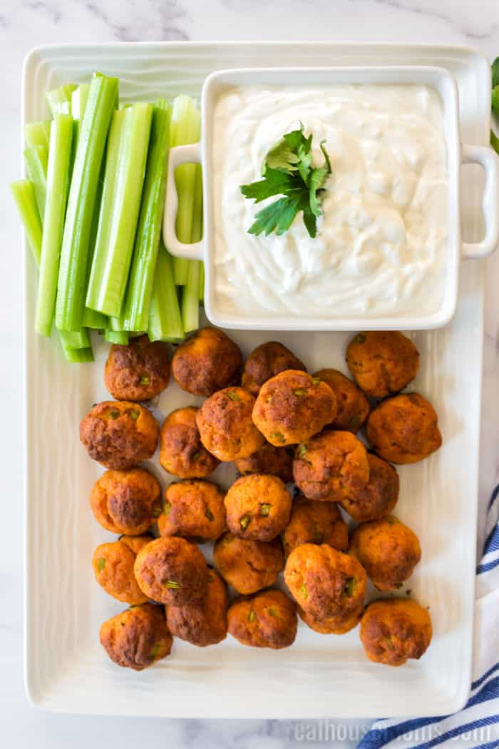buffalo chicken meatballs with blue cheese sauce on a platter with celery sticks
