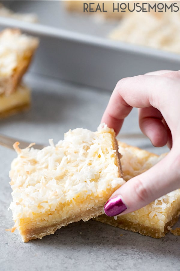 A hand reaching for a Buttery Coconut Bar