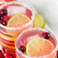one pic collage of cranberry margarita with two glasses of margarita next to each other both with salt rim lime and cranberry for garnish