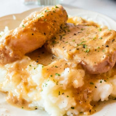 Close up of crock pot pork chops with mashed potatoes