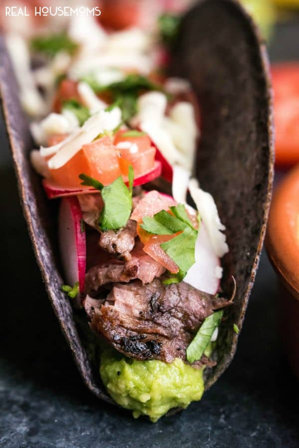 Close up of Carne Asada Tacos layered with guacamole, flank steak, radishes, and cilantro