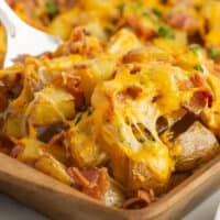 cheesy bacon oven potatoes on a bakign sheet with a spatula lifting some up with recipe name at bottom