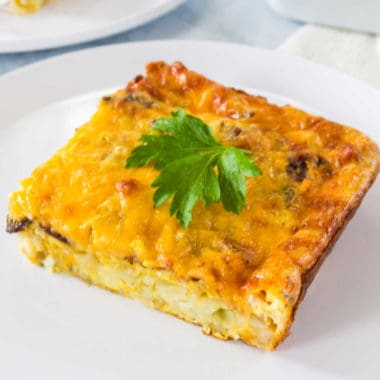 Hash browns layered with all your breakfast favorites & then baked to perfection make this Cheesy Breakfast Casserole with Bacon & Eggs a yummy brunch dish!