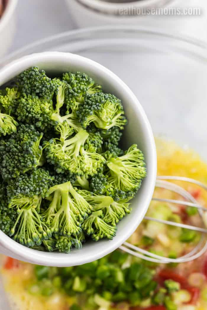 broccoli being poured into a mixing bowl