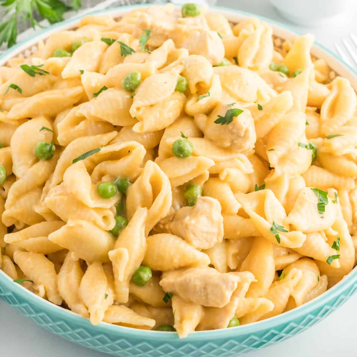 square image of blue serving bowl with cheesy instant pot chicken pasta