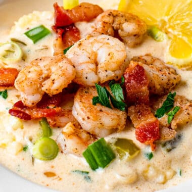 square image of shrimp and cheesy grits in a bowl with chopped green onion