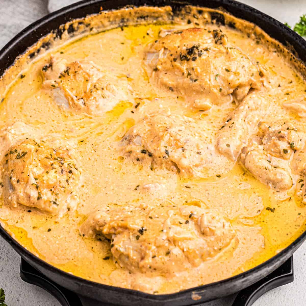 square image of cheesy skillet ranch chicken thighs in a cast iron skillet