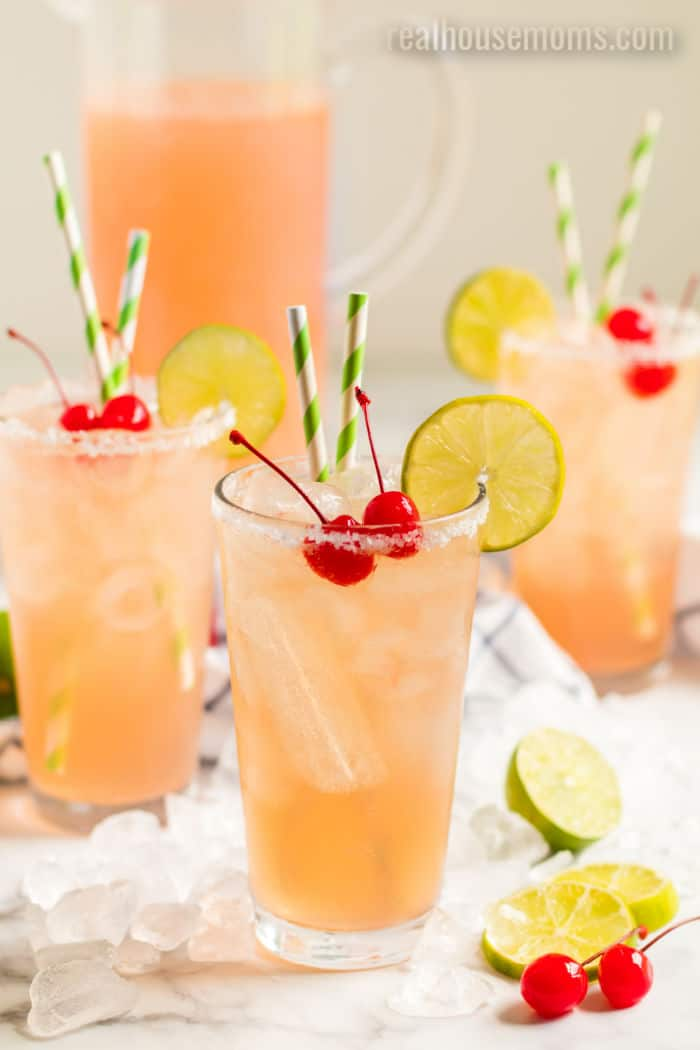 cherry beer margaritas in glasses rimmed with salt and garnished with lime slices and cherries