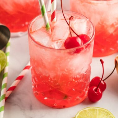 square image of 3 glasses of cherry poke cake cocktails with cherries and lime slices