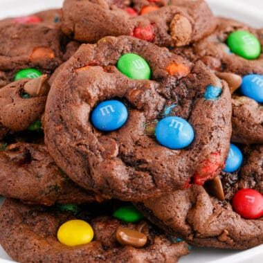 square image of cake mix chocolate M&M cookies piled on a plate