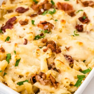 square image of chicken bacon ranch pasta bake with parsley and bacon on top