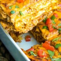 slice of chicken enchilada casserole being lifted from baking dish