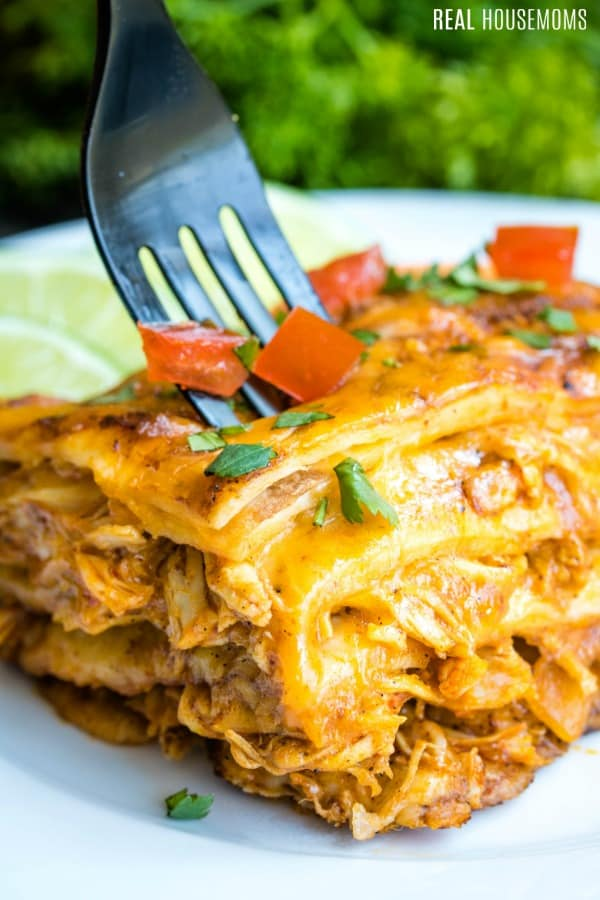 fork being sunk into a slice of chicken enchilada casserole