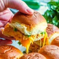 Hand lifting a Chicken Enchilada Slider out of the baking dish with lots of gooey cheese pulling long with the sandwich