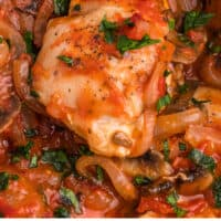 chicken marengo on a serving spoon over the baking dish with recipe name at the bottom