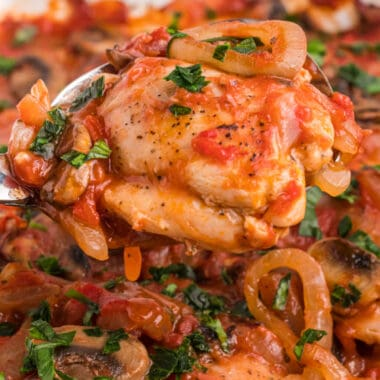 square image of chicken marengo on a serving spoon over the baking dish