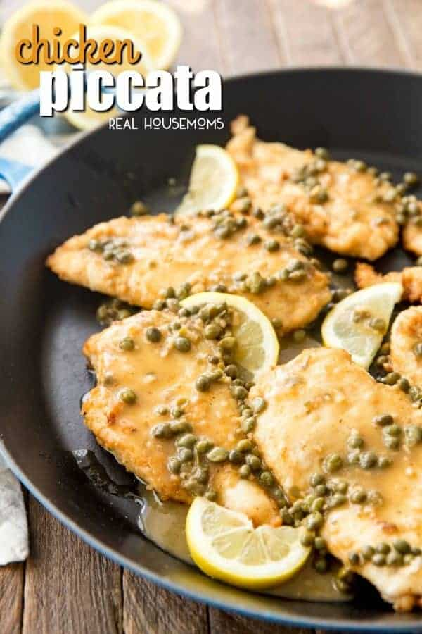 Finished Chicken Piccata in the skillet with lemon wedges