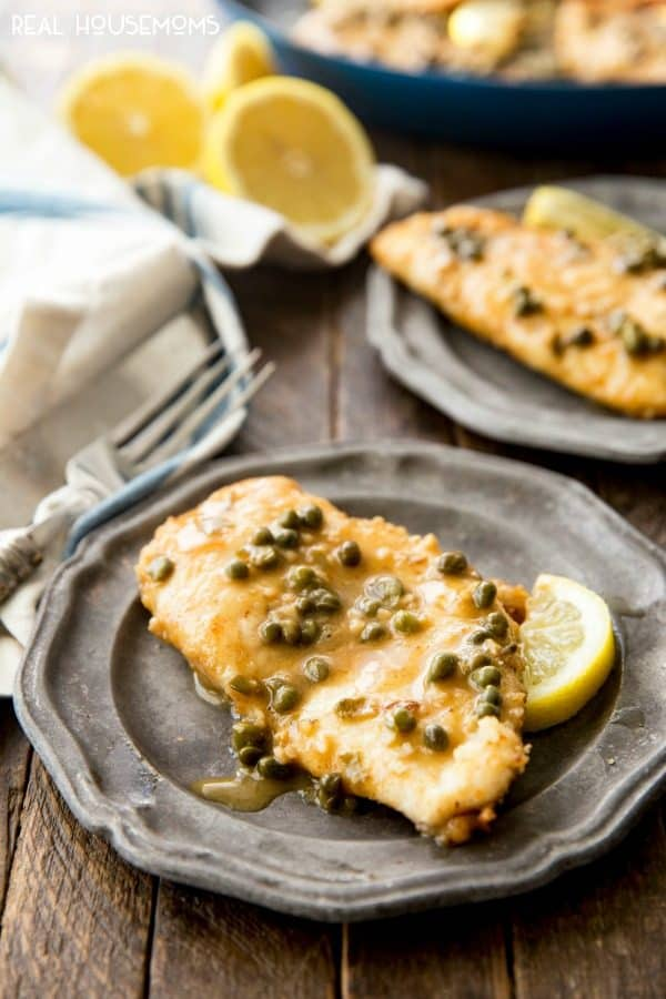 Chicken Piccata on a dinner plate with a lemon wedge