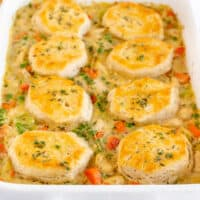 square image of chicken pot pie casserole topped with biscuits