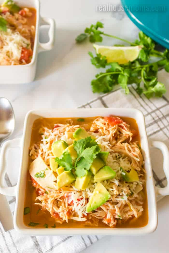 chicken tortilla soup topped with cheese, avocado, and cilantro