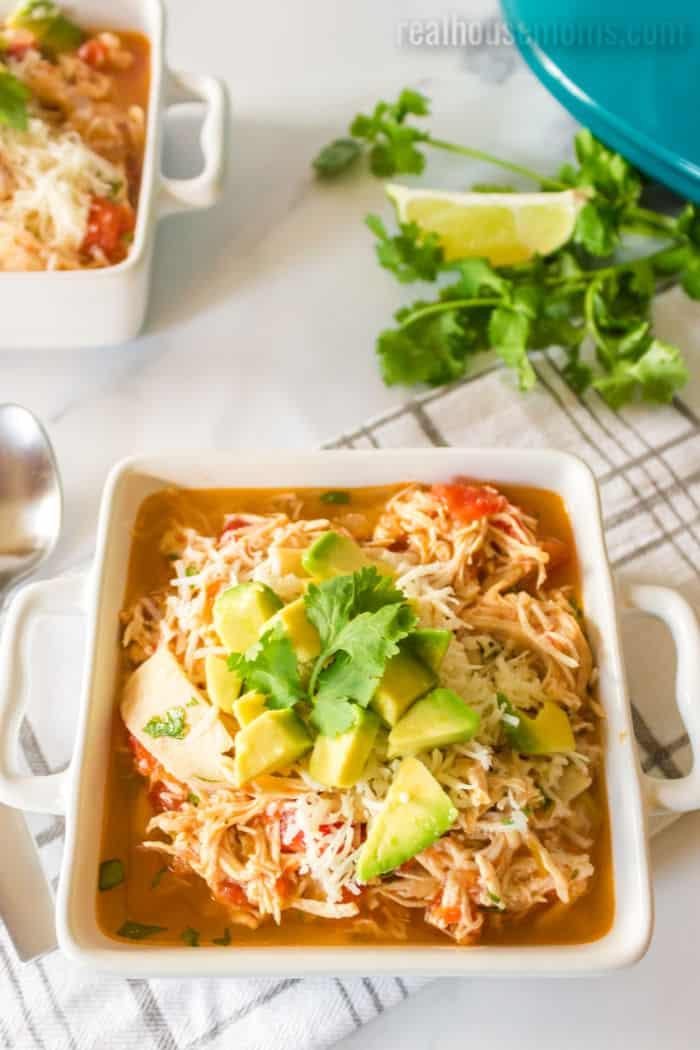 chicken tortilla soup topped with cheese, avocado, and cilantro