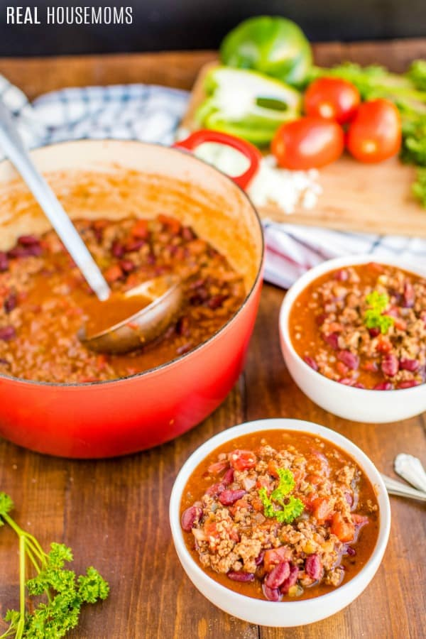 a pot of chili con carne with a ladle alongside bowls of chili garnished with parsley