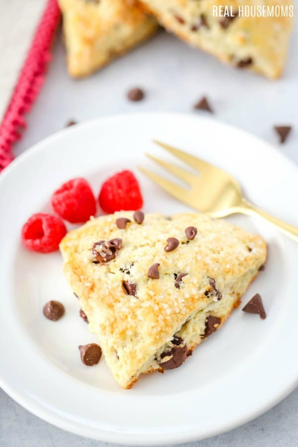 chocolate chip scone on a plate with raspberries