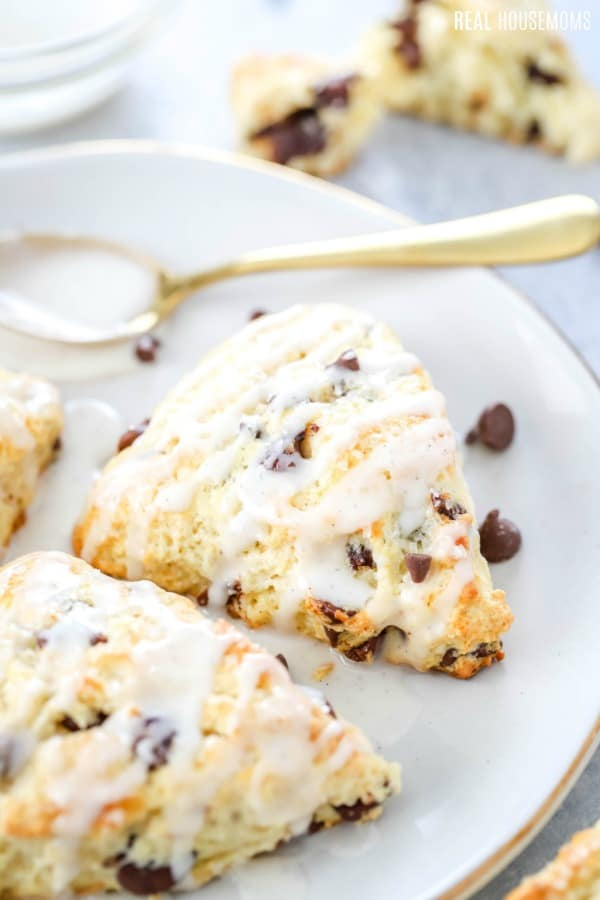 chocolate chip scones on a plate drizzled with vanilla glaze