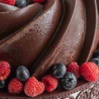 chocolate pound cake topped with berries on a cake stand with recipe name at the bottom