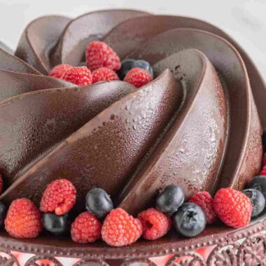 square image of chocolate coated chocolate pound cake with berries on a cake stand