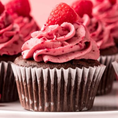 square image of chocolate raspberry cupcakes on a cake stand