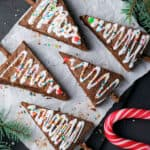 square image of christmas tree brownies laid out on a piece of parchment paper next to a candy cane