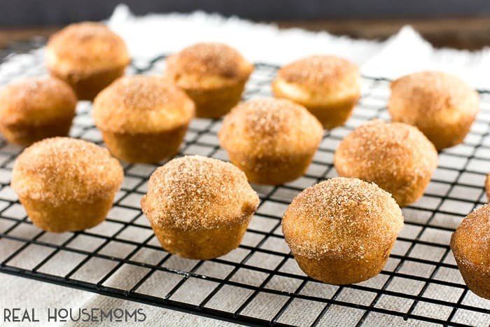 Churro Muffins lined up on a cooling rack after being dipped in cinnamon & sugar