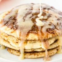 stack of cinnamon roll pancakes with cream cheese glaze being poured over top with recipe name at bottom