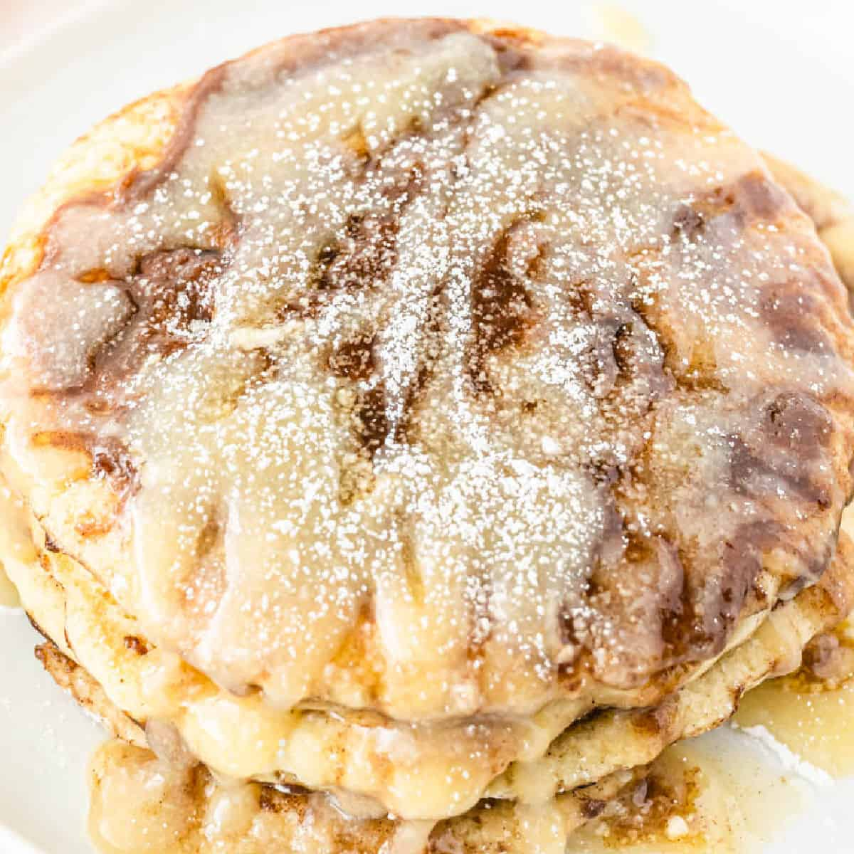 square image of a stack of cinnamon roll pancakes with cream cheese glaze