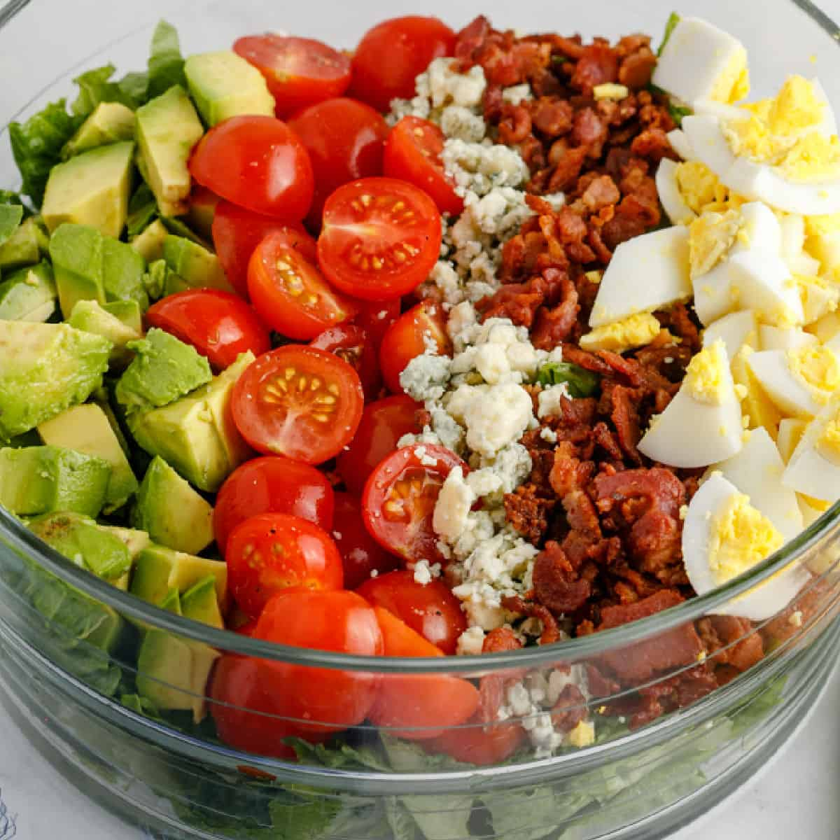 square image of cobb salad in a glass bowl with toppings arranged in lines