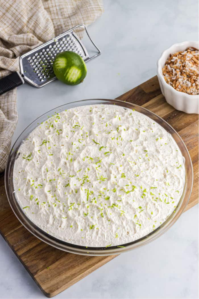 lime zest sprinkled over homeade whipped cream on a pie