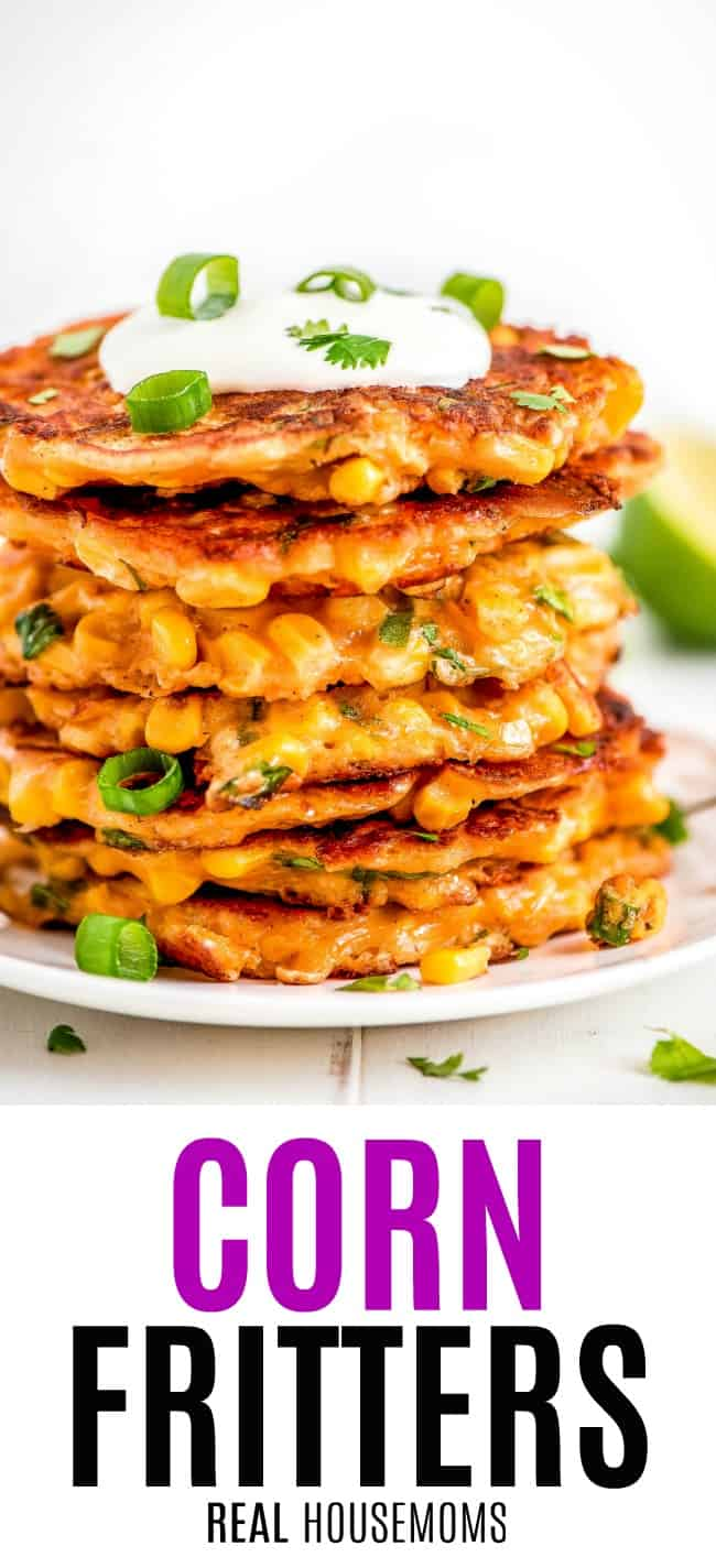 corn fritters stacked up on a plate garnished with sour cream and green onion