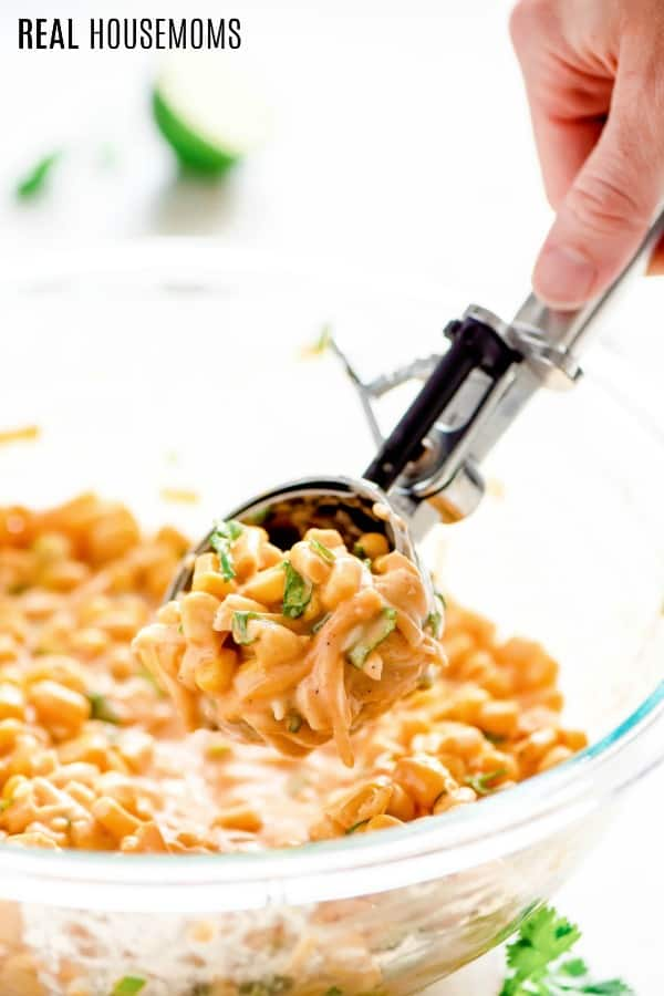 corn fritter mix in a bowl being scooped out for cooking