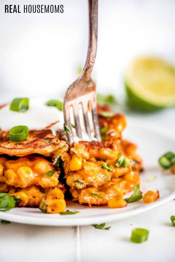 corn fritters stacked up with a fork taking out a bite