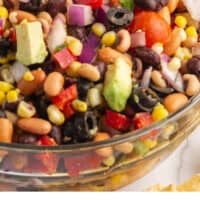 tortilla chip stuf into a bowl of cowboy caviar with recipe name at bottom