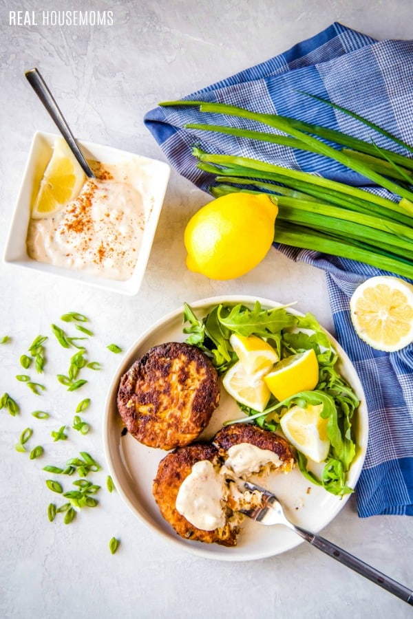 crab cakes on a plate with lemons and greens next to a bowl of remoulade sauce