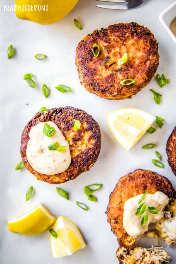 crab cakes on a serving platter garnished with remoulade sauce and green onion
