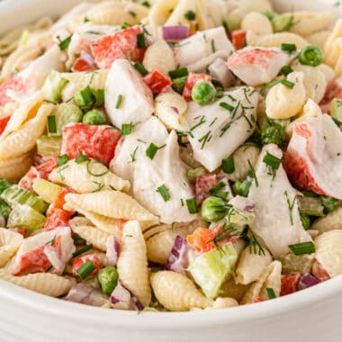 square close up image of crab pasta salad in a serving bowl
