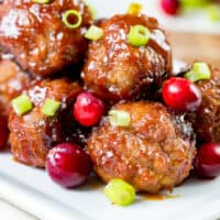 square image of cranberry bbq meatballs on a serving plate with fresh cranberries and sliced green onion