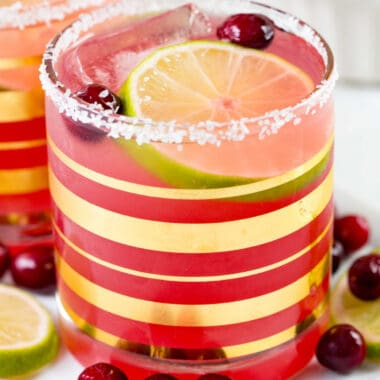 square image of cranberry margarita in a rocks glass with salt rim