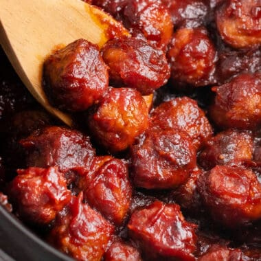square image of a wooden spoon with cranberry meatballs on it