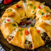 square image of a cream cheese & sausage crescent roll ring with dice red bell pepper and parsley on top