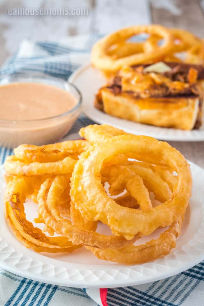onion rings on a plate next to fry sauce and a hot dog