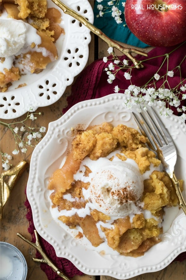 Servings of Crock Pot Apple Cobbler on dessert plates with forks and topped with ice cream and cinnamon